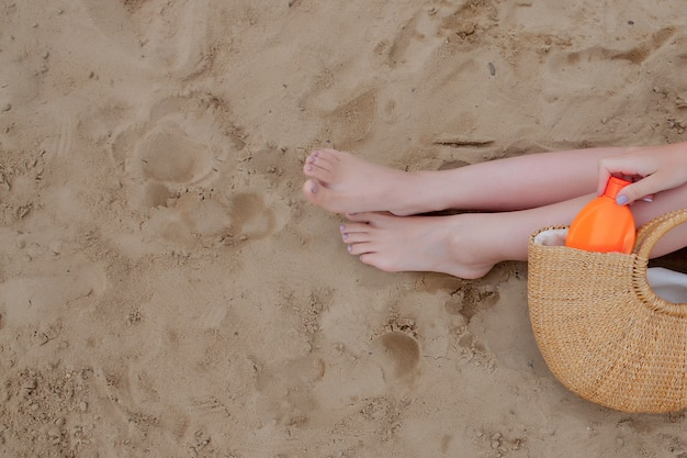 Spruzzo di olio per ragazza abbronzando la protezione delle gambe dai raggi uv del sole mettendo crema solare crema solare.