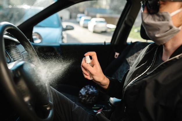 Spruzzo spray disinfettante antibatterico sul volante, auto per disinfezione, concetto di controllo delle infezioni. prevenire il coronavirus, covid-19, influenza. uomo che indossa in maschera protettiva medica alla guida di un'auto.