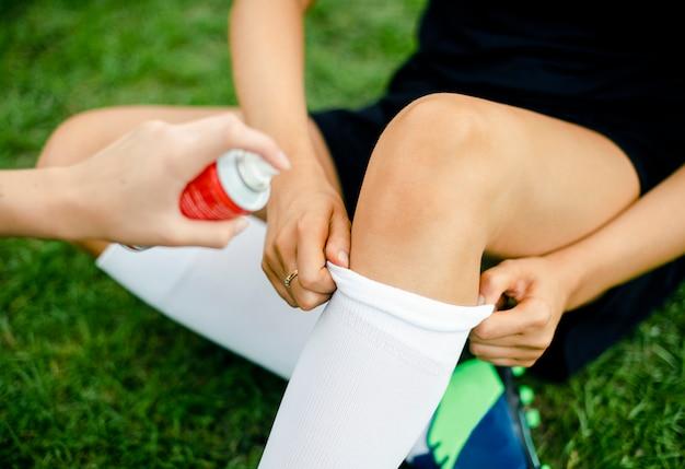 Spruzzo spray rinfrescante su un ginocchio di giocatori di football