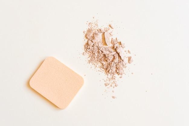 Spugna cosmetica e polvere spolverata. il concetto di trucco, cosmetici per il viso, cura della pelle. minimalismo, vista dall'alto.