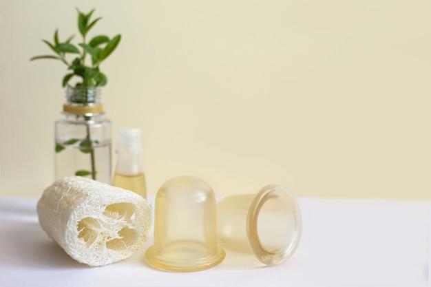 Spugna di luffa, vasetti di silicone e olio per massaggi. accessori per massaggio corpo anticellulite e linfatico
