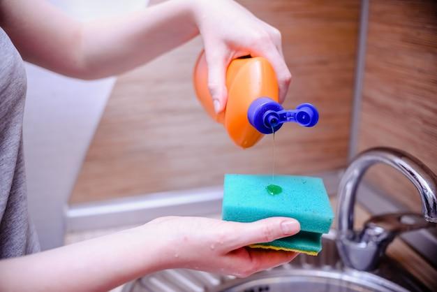 Spugna per piatti con sapone per piatti. concetto di pulizia della casa.