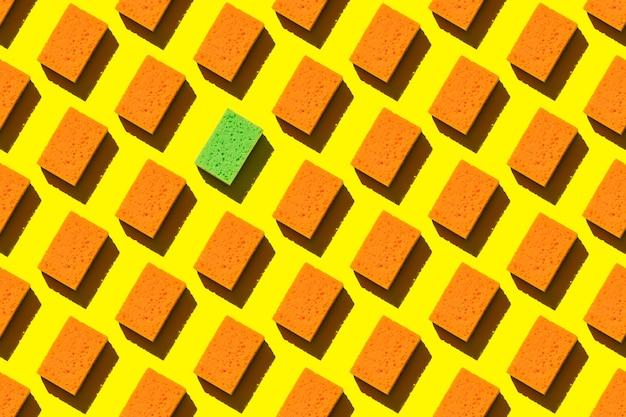 Spugne arancioni senza cuciture per lavare i piatti su uno sfondo giallo