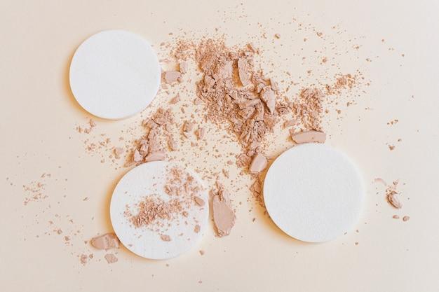 Spugne cosmetiche e polvere in polvere. il concetto di trucco, cosmetici per il viso, cura della pelle. minimalismo, vista dall'alto.