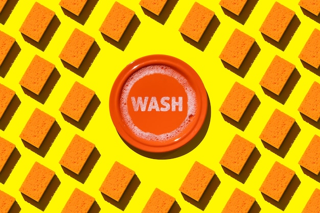 Spugne per stoviglie arancione senza cuciture e piatto arancione con acqua e schiuma
