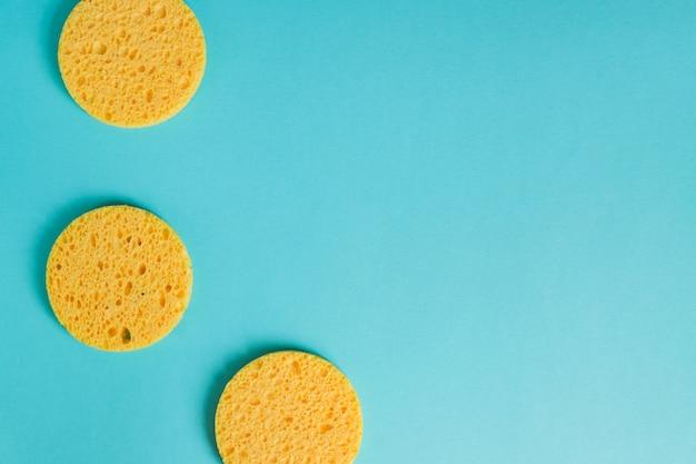 Spugne rotonde gialle su fondo blu pastello, cura facciale. dispositivo cosmetico. pulizia profonda della pelle.