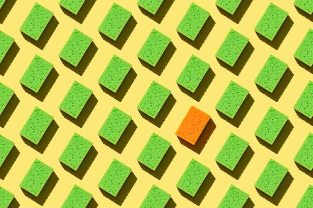 Spugne verdi senza cuciture per lavare i piatti su uno sfondo giallo