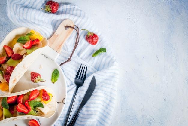 Spuntini. cibo per una festa. tacos alla frutta con fragole, mango, banane, cioccolato, menta