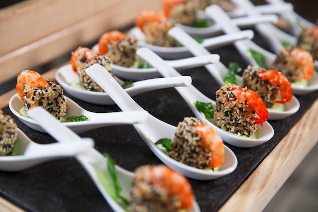 Spuntini con gamberetti in cucchiai sul tavolo del buffet