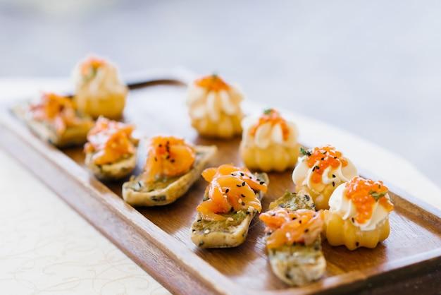Spuntini con i salmoni o i salmoni su una fine di legno del bordo o del piatto su con il fuoco selettivo