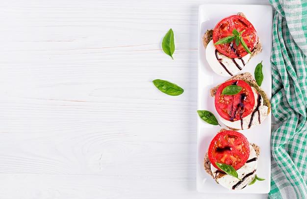 Spuntini con mozzarella, pomodori e pane di segale sulla tavola di legno bianca. vista dall'alto