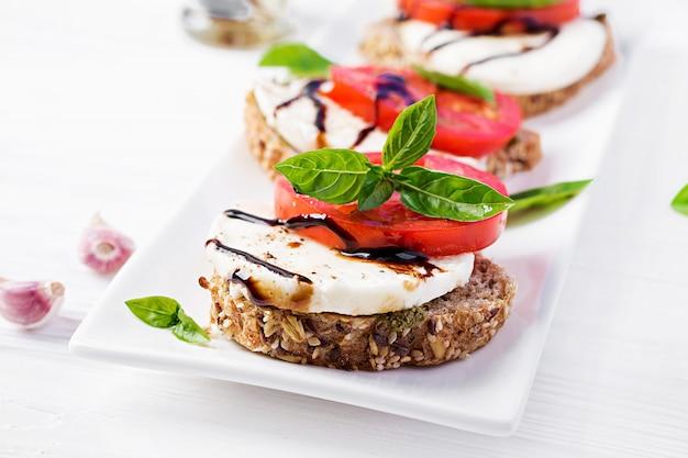 Spuntini con mozzarella, pomodori e pane di segale sulla tavola di legno bianca.