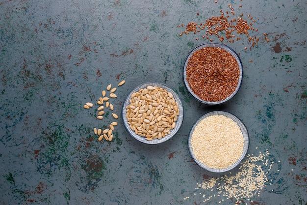 Spuntini con semi di girasole, semi di lino, semi di sesamo su grigio