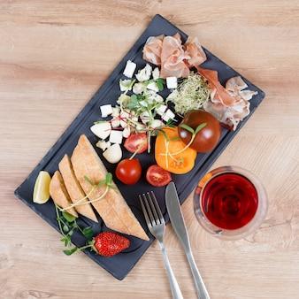 Spuntini con vino rosso sul bordo nero dell'ardesia sopra la tavola di legno. prelibatezza e cibo semplice, pane, formaggio, pomodori e jamon.