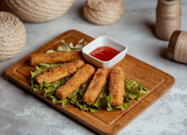 Spuntini croccanti del dito di pollo, bastoni con ketcup su un bordo di legno