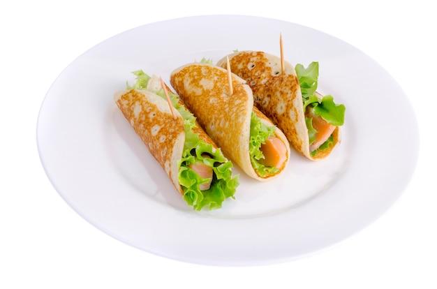 Spuntini da pancake, salmone e foglie di insalata verde.