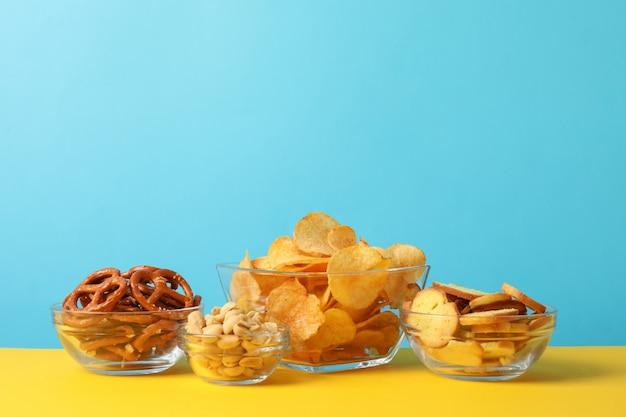 Spuntini della birra, patatine fritte, cracker in una ciotola su giallo contro il blu, spazio per testo