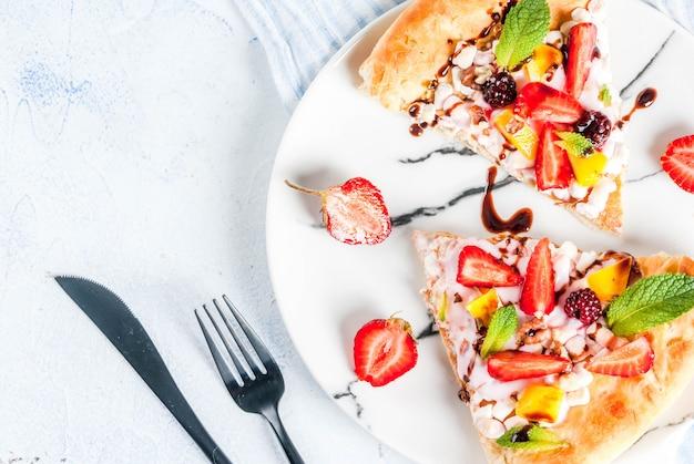 Spuntini estivi. cibo per la festa. pizza alla frutta con panna, ribes, yogurt, fragole, mango, pesche, banane, more, cioccolato, noci, menta. sul tavolo azzurro.