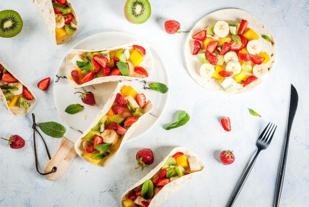 Spuntini estivi. cibo per una festa. tacos alla frutta con fragole, mango, banane, cioccolato, menta. su un tavolo di cemento azzurro. vista dall'alto di copyspace