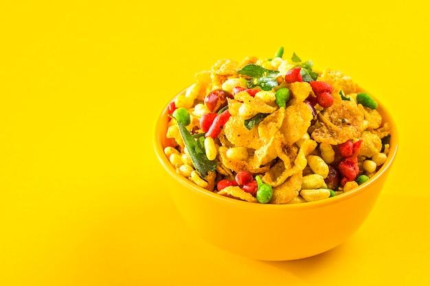 Spuntini indiani: piatto salato fritto indiano tradizionale chiamato chivda o miscela o farsan fatto di farina di grammo e mescolato con frutta secca e noci tostate con sale, pepe, legumi, spezie e piselli