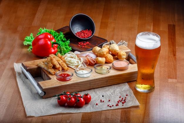 Spuntini per birra comprende palle di formaggio fritto, formaggio di maiale, prosciutto e bastoncini di granchio su una tavola di legno