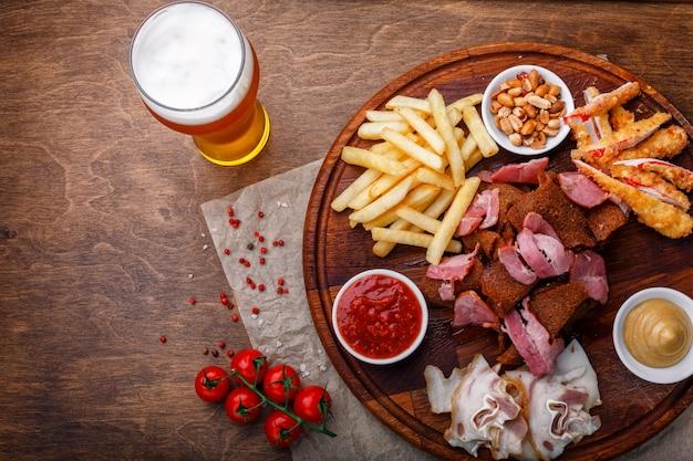 Spuntini per birra o alcol e comprende carne di maiale affumicata, patatine fritte, pane fritto, bastoncini di granchio e noci