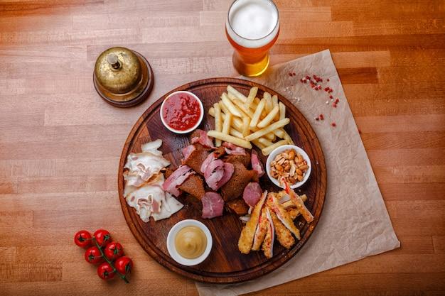Spuntini per birra o alcol e comprende carne di maiale affumicata, patatine fritte, pane fritto, bastoncini di granchio
