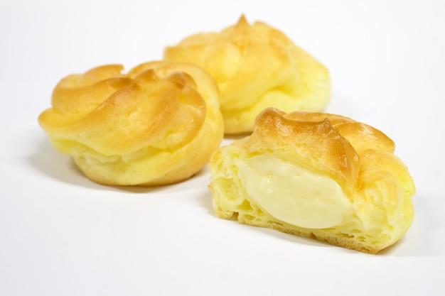 Spuntini per dessert eclair rivela la crema. su uno sfondo bianco