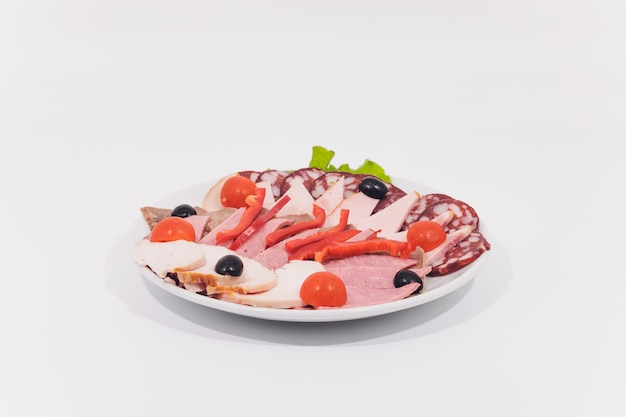 Spuntini salati differenti in una ciotola e in un fondo bianco.