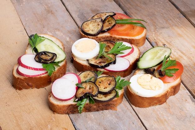 Spuntini sani con hummus, spinaci e pomodori sulla tavola di legno leggera, fine su