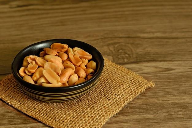 Spuntino arrostito delle arachidi in piccola ciotola sul sacco e sulla tavola di legno