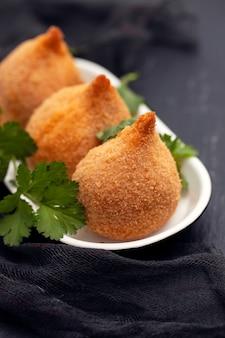 Spuntino brasiliano coxinha de frango sul piatto