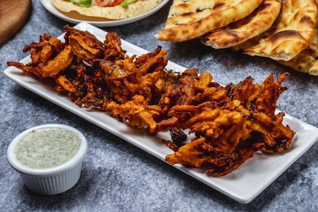 Spuntino fritto nel grasso bollente croccante dello spuntino di vista laterale con salsa e pane sulla tavola