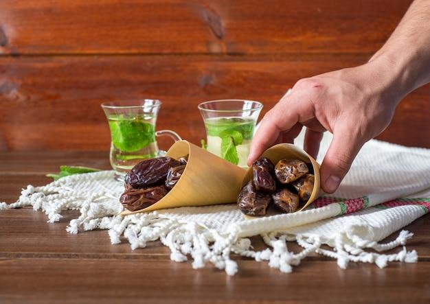 Spuntino iftar o suhoor, mano di un uomo con un cono di datteri con tè al mentha, concetto di ramadan