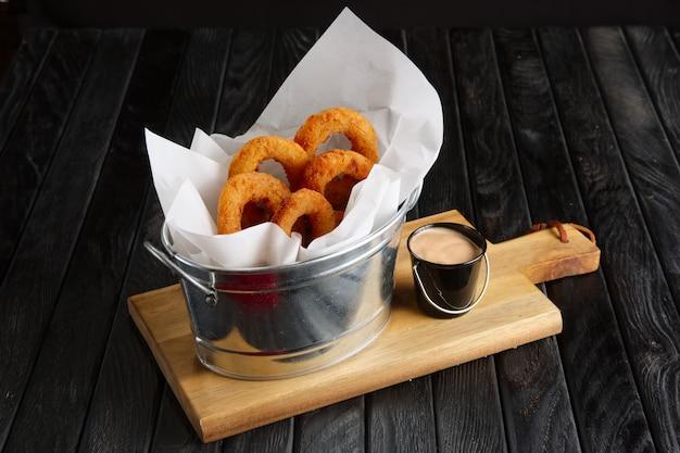 Spuntino per la birra. anelli di cipolla fritti con salsa servita in metallo