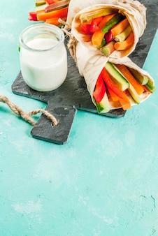 Spuntino salutare estivo, sandwich alla tortiglia in stile messicano avvolge assortiti bastoncini di verdure fresche colorate (sedano, rabarbaro, pepe, cetriolo e carota) con salsa allo yogurt tuffo sfondo azzurro