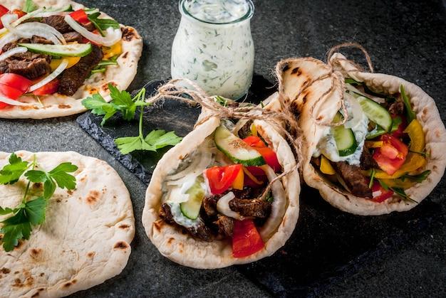 Spuntino salutare, pranzo. gyros sandwich tradizionali greci avvolti - tortillas, pita di pane con ripieno di verdure, carne di manzo e salsa tzatziki