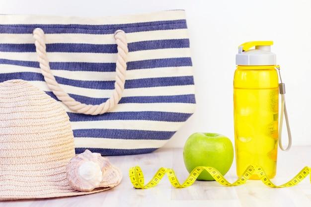 Spuntino sano, nastro di misurazione e bottiglia d'acqua su una superficie di legno leggera. preparazione per la stagione estiva e il concetto di spiaggia, borsa da spiaggia, cappello e conchiglie, perdita di peso e sport