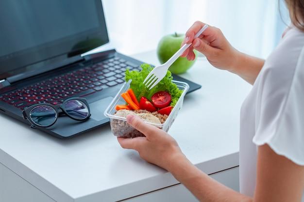 Spuntino sano sul posto di lavoro dell'ufficio. la donna di affari che mangia i pasti da porta via la scatola di pranzo allo scrittorio funzionante durante l'intervallo di pranzo