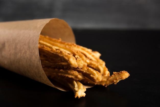 Spuntino spagnolo di churros in una carta da imballaggio