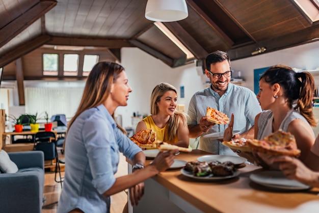 Squadra amichevole di affari che mangia pizza insieme nell'ufficio coworking.