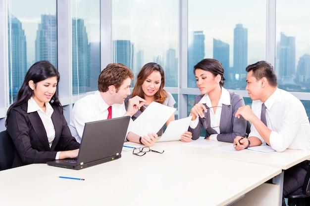 Squadra asiatica di affari nella riunione di strategia