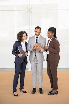 Squadra concentrata di affari che sta nel corridoio dell'ufficio
