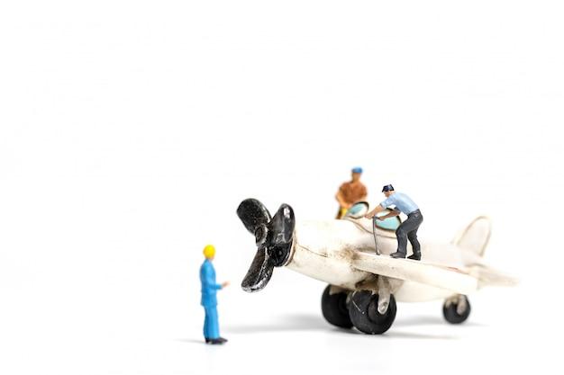 Squadra del lavoratore che ripara l'aeroplano del giocattolo su fondo bianco
