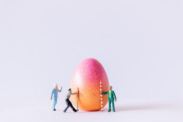 Squadra del lavoratore della gente miniatura che lavora alle uova di pasqua per il fondo di giorno di pasqua