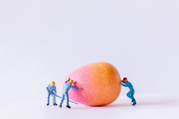 Squadra del lavoratore della miniatura che lavora alle uova di pasqua per il giorno di pasqua