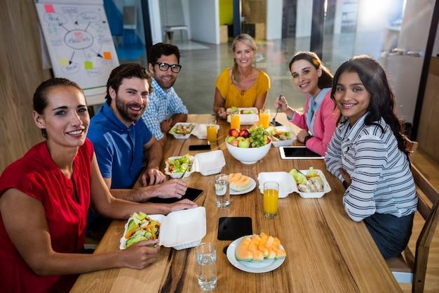 Squadra di affari casuali che mangia insieme