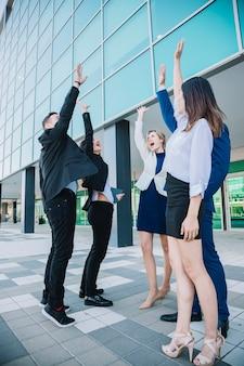 Squadra di affari che alza le mani