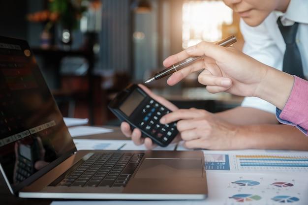Squadra di affari che analizza i grafici ed i grafici di reddito
