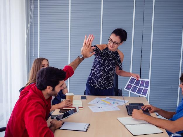 Squadra di affari che celebra la vittoria in ufficio, successo aziendale